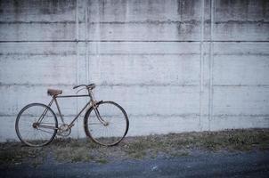 antikes oder retro oxidiertes Fahrrad draußen auf einer Betonwand foto