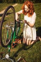 rothaarige Frau repariert ein Fahrrad foto