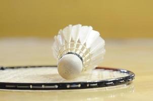 weißer Federball legte sich auf Schläger in der Turnhalle foto