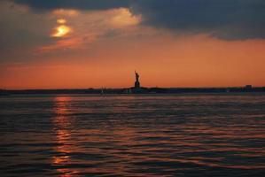 Freiheitsstatue in der Abenddämmerung silhouettiert - New York foto
