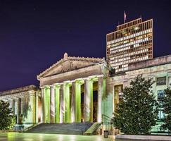 ein Nachtfoto des Kriegsdenkmals mit einem Gebäude dahinter