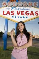 Frau, die vor Las Vegas Zeichen aufwirft foto