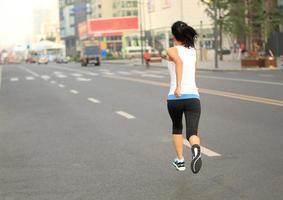 Fitness-Sportfrau des gesunden Lebensstils, die auf Stadtstraße läuft