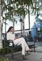 Geschäftsfrau mit PDA auf Bank foto
