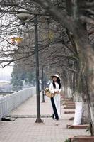 das Mädchen in vietnamesischer traditioneller Kleidung, die auf Straßenseite geht foto