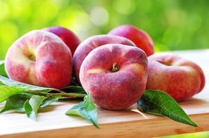 frische Pfirsiche und Blätter auf dem Tisch foto