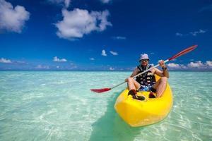 junger kaukasischer Mann, der im Meer auf den Malediven Kajak fährt