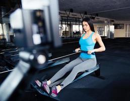 Frau, die Übung auf Simulator im Fitnessstudio macht foto