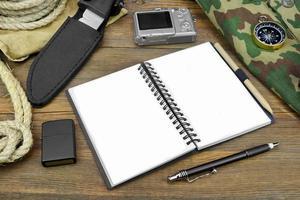 Reisevorbereitung. offenes Notizbuch, Kamera, Seil, Kompass, Stift,