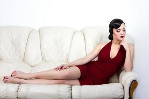 Brünette Frau im Retro-Stil, die auf dem Sofa liegt