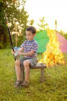 Kind auf Campingausflug lernt wie man; Angelrute verwenden foto