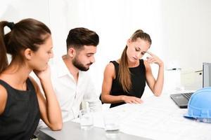Geschäftsmannarchitekt, der mit Blaupause im Büro-Besprechungsraum diskutiert foto
