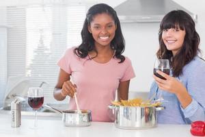 glückliche Freunde, die gemeinsam das Abendessen vorbereiten