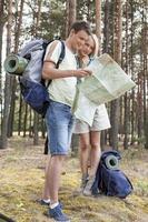 volle Länge des jungen Wanderpaares, das Karte im Wald liest foto