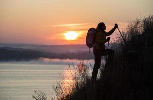 Silhouette des aufsteigenden steilen Hügels des Rucksacktouristen
