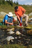 Männer, die Wasser aus dem Gebirgsbach filtern 4