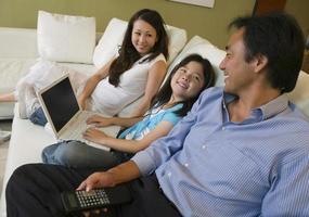 Familie sitzt auf dem Sofa foto