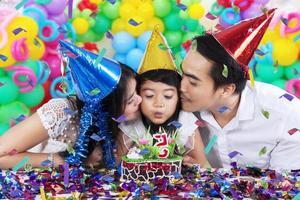 glückliche Familie, die eine Geburtstagskerze bläst foto