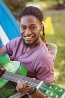 glücklicher Hipster, der an der Kamera lächelt, die Gitarre spielt
