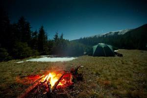 Kamin während der Ruhe in der Nähe von Zelt in der Nacht foto
