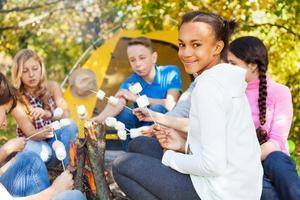 Jugendliche mit Marshmallow-Stöcken sitzen in der Nähe von Lagerfeuer foto