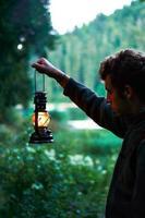 Mann, der Laterne im Garten hält foto