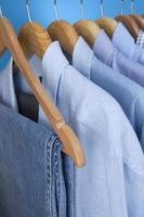 blaue Herrenhemden und Jeans auf Kleiderbügeln foto