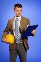 Geschäftsmann, der Helm hält und Zwischenablage betrachtet foto