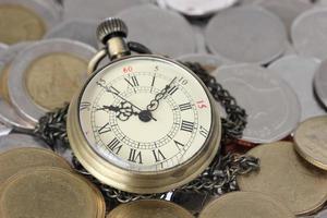 Finanzkonzept, alte Uhr mit Münzen foto