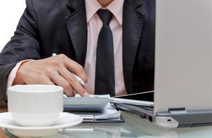 Geschäftsmann, der die Informationen mit Laptop berechnet foto