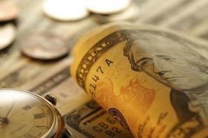 Nahaufnahme einer kleinen Uhr und eines Bündels Bargeld, foto