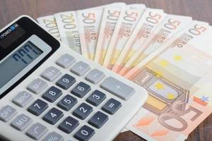 Taschenrechner und Banknoten auf dem Tisch foto