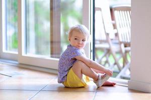 Kleinkindmädchen, das Schuhe setzt, die auf Boden neben Fenster sitzen foto