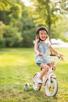 Porträt des glücklichen kleinen Mädchens, das Fahrrad draußen im Park reitet foto