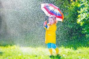 lustiges Kleinkind mit Regenschirm, der im Regen spielt foto