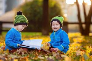 zwei Jungen, die nachmittags ein Buch über Rasen lesen foto