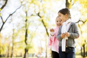 zwei kleine Mädchen im Herbstpark foto