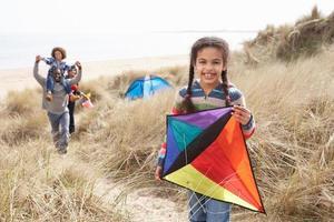 Familie hat Spaß mit Drachen in Sanddünen foto