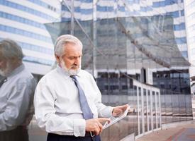älterer Geschäftsmann, der digitales Tablett verwendet