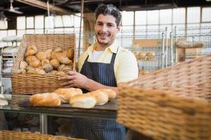 Porträt des glücklichen Arbeiters, der Brot hält foto