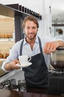 hübscher Barista, der der Kamera eine Tasse Kaffee anbietet