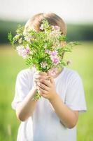 Junge versteckt sich durch Blumenstrauß