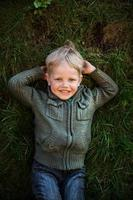 kleines Kind, das auf Gras liegt und lächelt