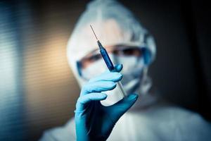 Forscher im Schutzanzug, der eine Spritze vorbereitet