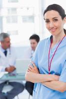 Krankenschwester verschränkt die Arme mit ihren Kollegen dahinter foto