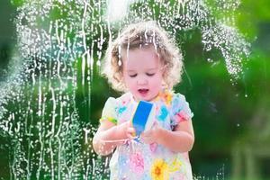 süßes kleines Mädchen, das ein Fenster wäscht foto