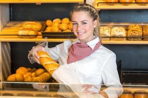 Ladenbesitzer in der Bäckerei, der Brotlaib in Papiertüte steckt foto