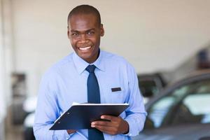 afrikanischer Verkäufer, der am Fahrzeugausstellungsraum arbeitet foto