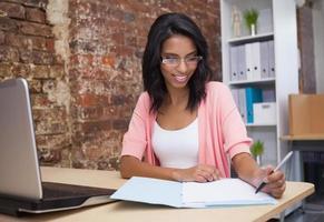 Frau, die Notizen mit Laptop schreibt foto