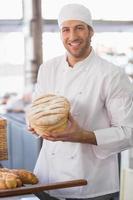 glücklicher Bäcker mit Brotlaib foto